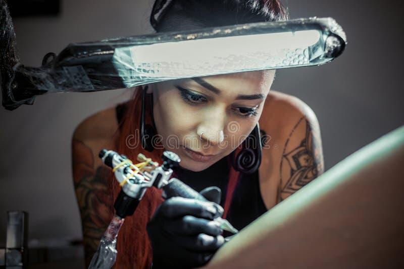 Maître de tatouage au travail Maître de tatouage de femme en cours de tatouage de création sous la lumière de lampe images libres de droits