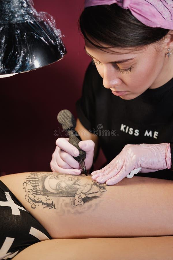 Maître femelle de tatouage tatouant le client féminin Nonnes de figure sur la cuisse Machine et lampe noires de tatouage Artiste  photos libres de droits