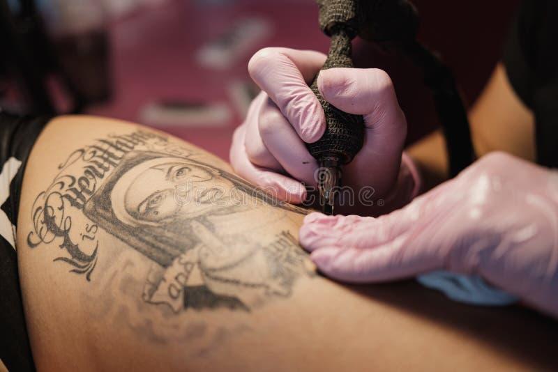 Maître femelle de tatouage tatouant le client féminin Nonnes de figure sur la cuisse Machine et lampe noires de tatouage Artiste  image stock