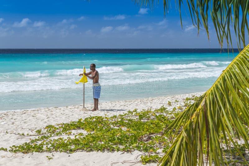 Maître nageur et drapeau jaune de précaution image libre de droits