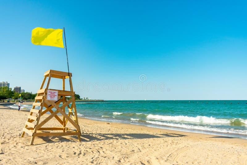 Maître nageur Tower avec le drapeau jaune sur une plage de Chicago semblant du nord photo stock