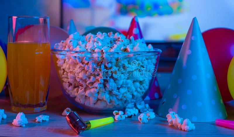 Maïs éclaté avec les accessoires de fête sur le fond de la TV TV de observation à l'occasion d'une célébration de famille ou en c images stock
