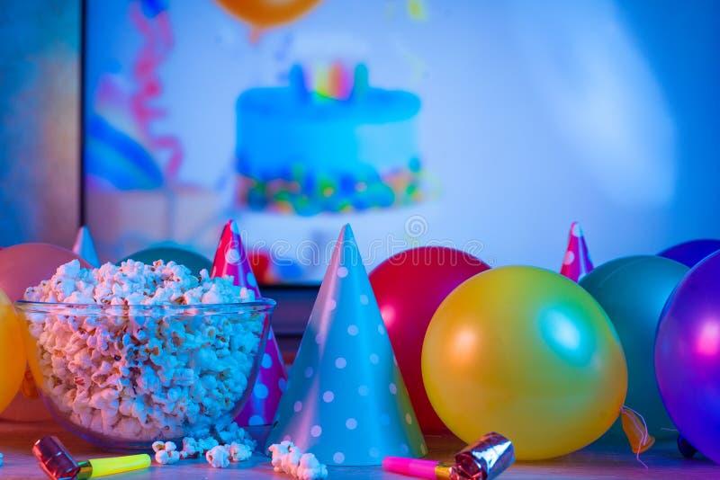Maïs éclaté avec les accessoires de fête sur le fond de la TV TV de observation à l'occasion d'une célébration de famille ou en c images libres de droits