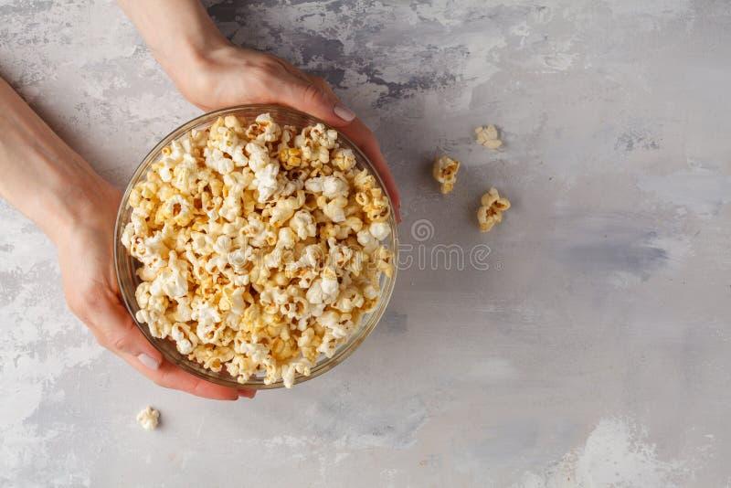 Maïs éclaté d'or de caramel dans le bol en verre dans des mains, vue supérieure, PS de copie photo libre de droits