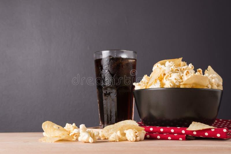 maïs éclaté de fromage dans la cuvette et les pommes chips sur le backgr en bois image stock