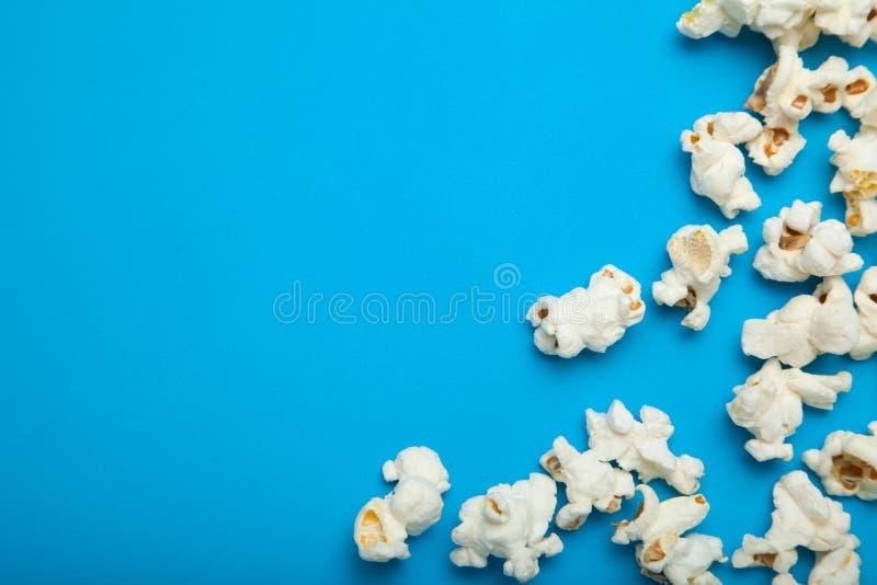 Maïs éclaté dispersé sur un fond bleu Copiez l'espace photos stock