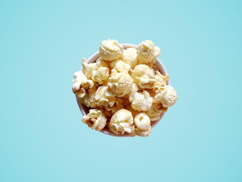 Maïs éclaté doux avec la saveur de caramel dans la cuvette de papier sur le fond bleu photos libres de droits