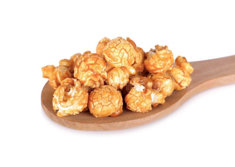 Maïs éclaté doux de caramel de beurre sur la cuillère en bois et sur le backgr blanc photo libre de droits