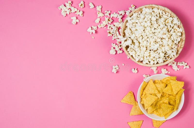 Maïs éclaté et pommes chips dans la cuvette sur la vue supérieure de fond rose photo stock