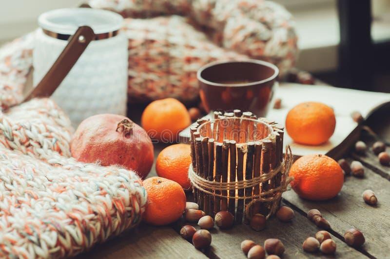 Mañana acogedora del invierno en casa con las frutas, las nueces y las velas, foco selectivo fotografía de archivo