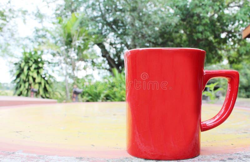 Mañana ascendente fresca de la taza roja en la tabla imagen de archivo libre de regalías