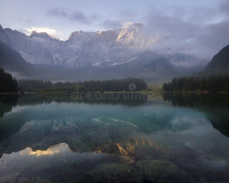 Mañana brumosa hermosa en un lago alpino fotografía de archivo