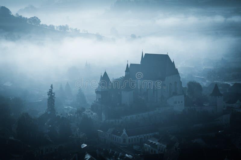 Mañana brumosa misteriosa sobre el pueblo de Biertan, Transilvania, Rumania imagen de archivo