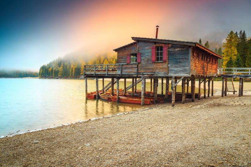 Mañana brumosa y lago espectacular con los barcos, lago Braies, Italia imagenes de archivo