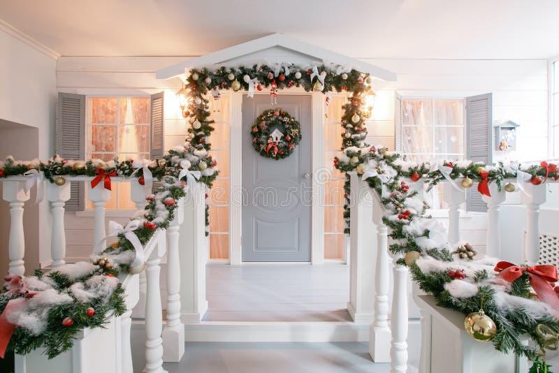 Mañana de la Navidad apartamentos de lujo clásicos con una chimenea blanca, árbol adornado, sofá brillante, ventanas grandes imagen de archivo libre de regalías