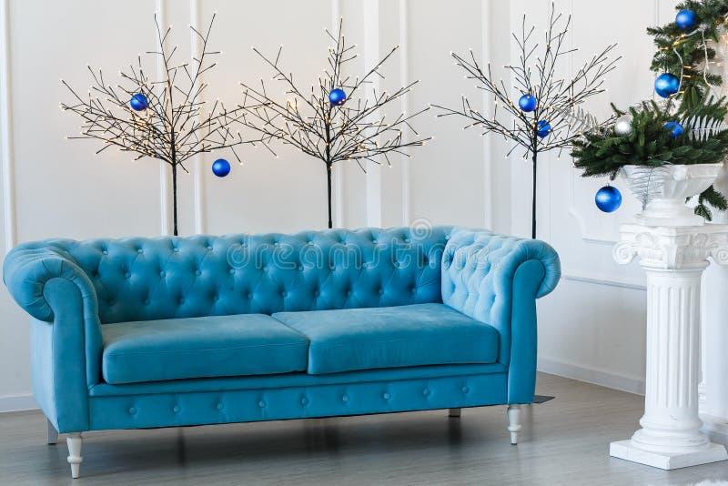 Mañana de la Navidad, espacio de la copia Apartamentos clásicos con el sofá abotonado azul, árbol de abeto adornado fotografía de archivo libre de regalías