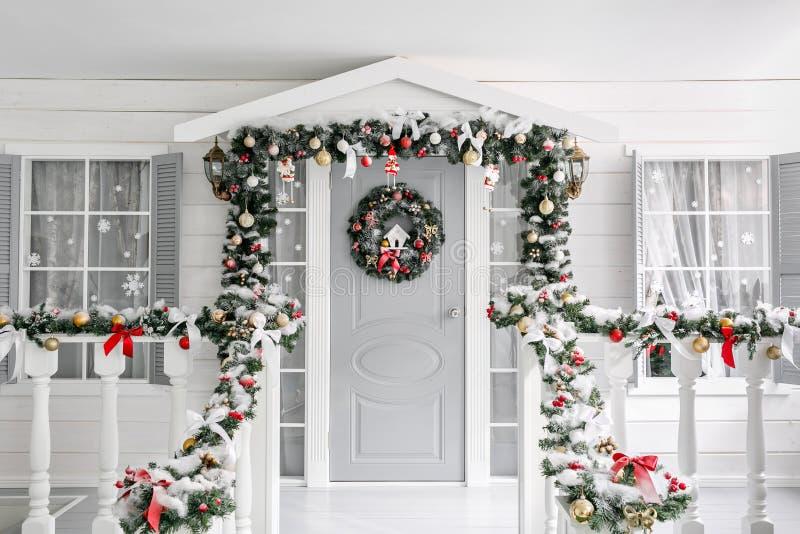 Mañana de la Navidad pórtico una pequeña casa con una puerta adornada con una guirnalda de la Navidad Cuento de hadas del inviern imagenes de archivo