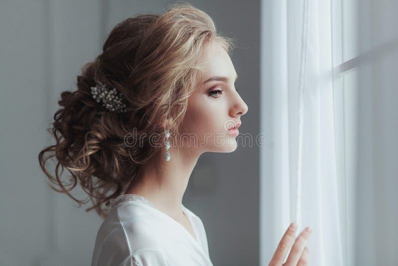 Mañana de la novia Mujer joven hermosa en traje blanco elegante con el peinado de la boda de la moda que se coloca cerca de imagen de archivo
