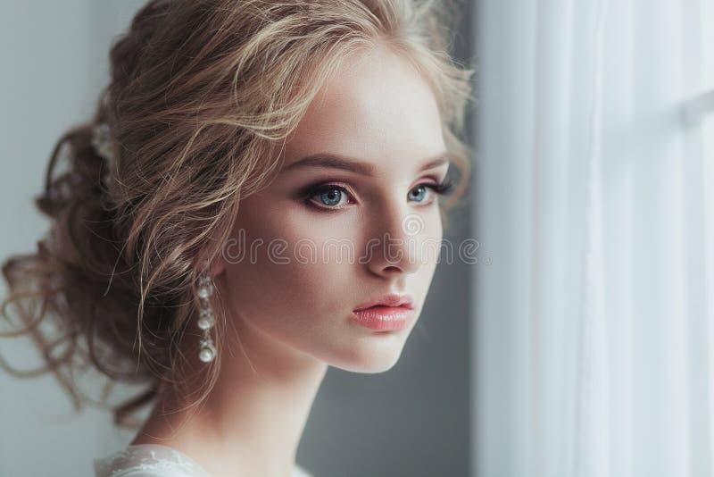 Mañana de la novia Mujer joven hermosa en traje blanco elegante con el peinado de la boda de la moda que se coloca cerca de imagenes de archivo