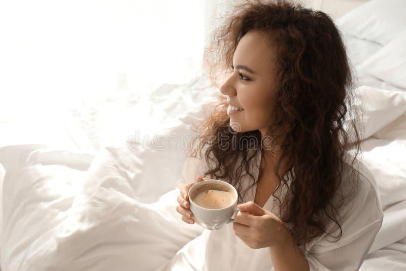 Mañana del café de consumición de la mujer afroamericana hermosa en casa imagen de archivo libre de regalías