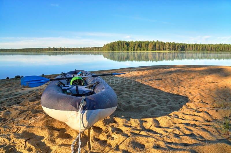 Mañana del comienzo del verano en el kajak que camina en la playa del lago foto de archivo