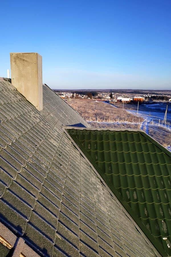 Mañana escarchada de la teja verde en el tejado de la casa foto de archivo libre de regalías