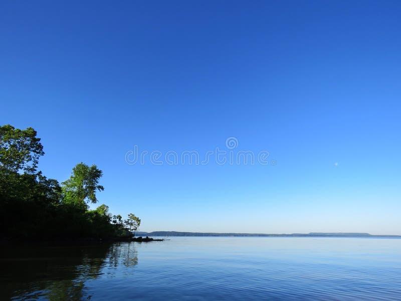 Mañana pacífica, lago en el amanecer, fondo tranquilo del lago con los árboles imagenes de archivo