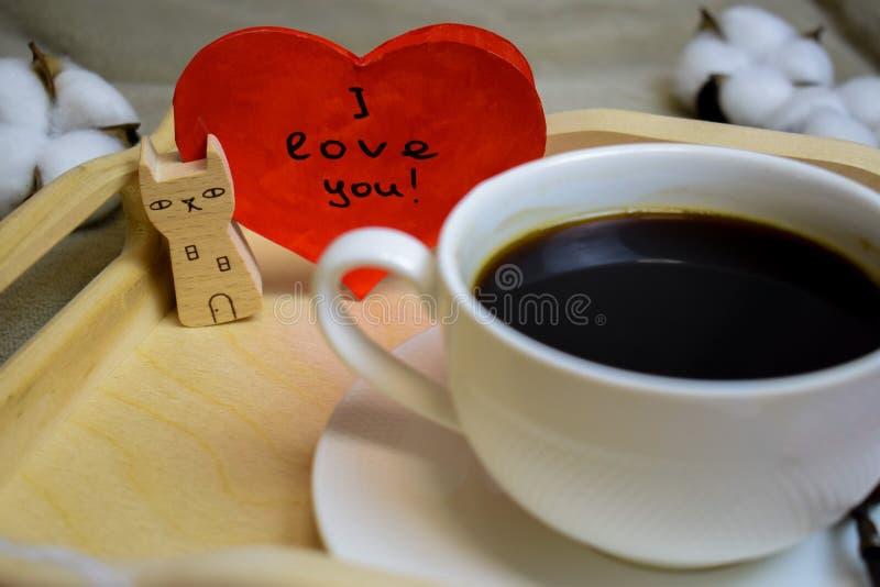 Mañana romántica el día de tarjeta del día de San Valentín - el café en cama en una bandeja de madera es una taza de café y un so imagen de archivo