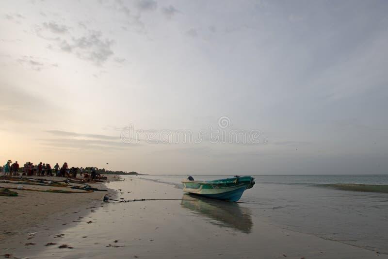 Mała łódź rybacka odbija w zmierzchu świetle na Nilaveli plaży w Trincomalee Sri Lanka obraz royalty free