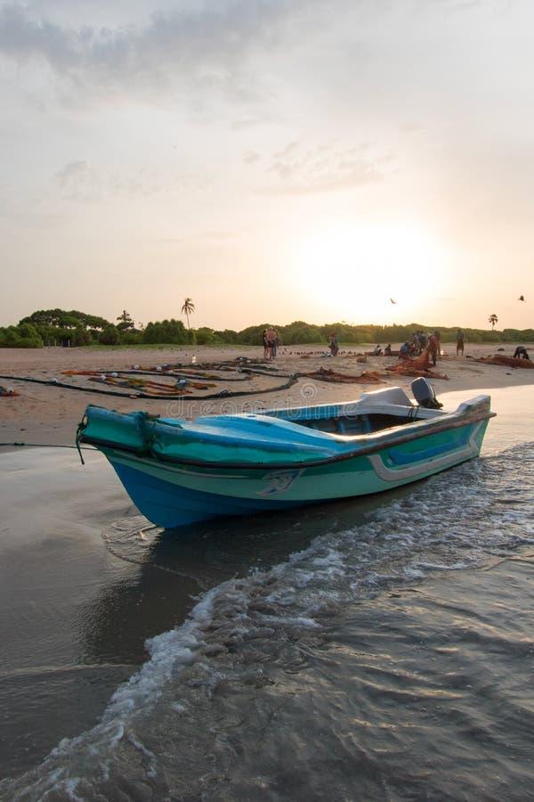 Mała łódź rybacka odbija w zmierzchu świetle na Nilaveli plaży w Trincomalee Sri Lanka obrazy stock
