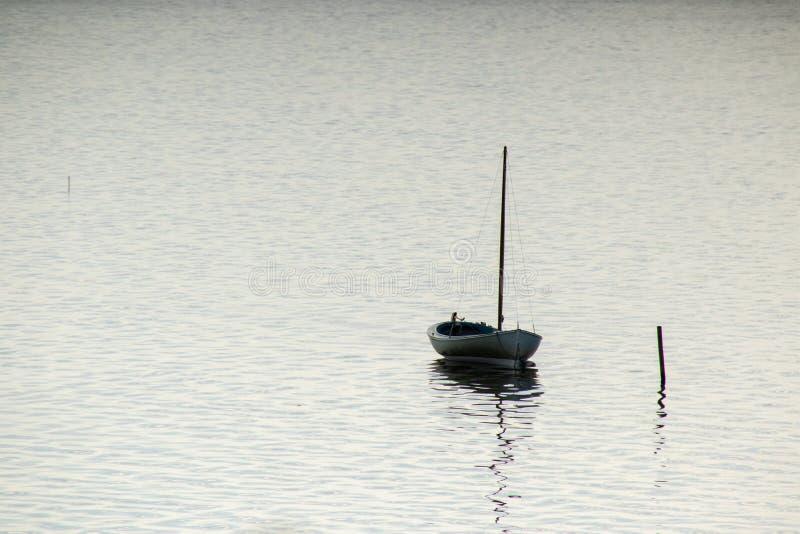 Mała łódka w spokojnym jeziorze fotografia stock