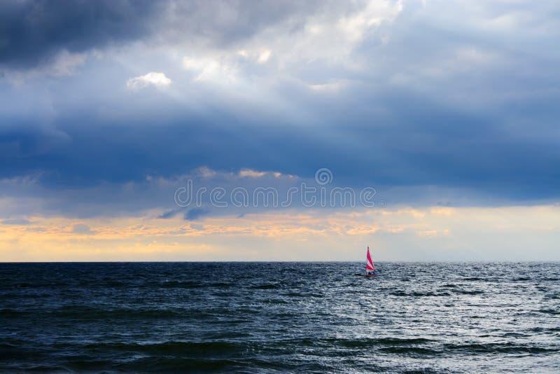 Mała łódka z żaglem na morzu pod burzowym niebem zdjęcia royalty free