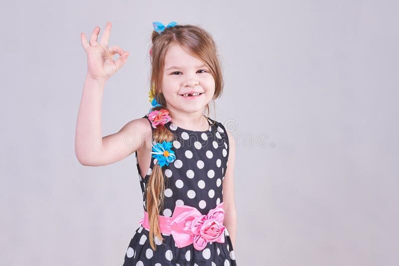 Mała ładna dziewczyna pokazuje ` OK ` zdjęcia stock