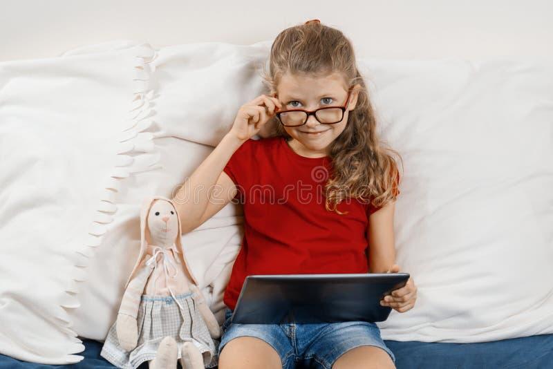 Mała ładna dziewczyna siedzi w domu w łóżku z pastylką, odpoczynkiem i edukacją w szkłach zabawkarską i cyfrową, w domu dziecko s fotografia stock