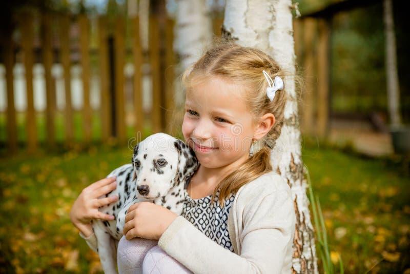 Mała śliczna blondynki dziewczyna bawić się z jej Dalmatyńskim szczeniaka outdoo na pogodnym ciepłym jesień dniu, opieka zwierzęc zdjęcia royalty free