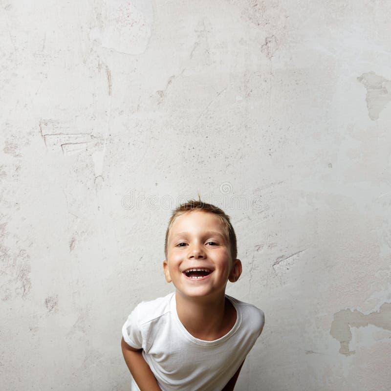 Mała śliczna chłopiec śmia się przy kamerą Cocrete zdjęcie royalty free