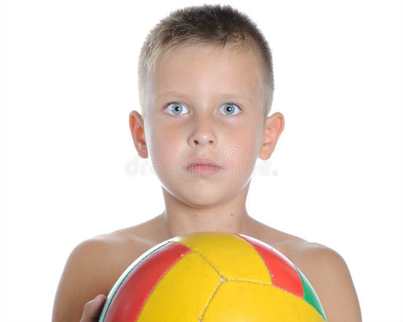 Mała śliczna chłopiec bawić się futbolową piłkę odizolowywającą fotografia royalty free