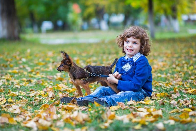 Mała śliczna chłopiec bawić się z jego psem w jesień parku obrazy royalty free