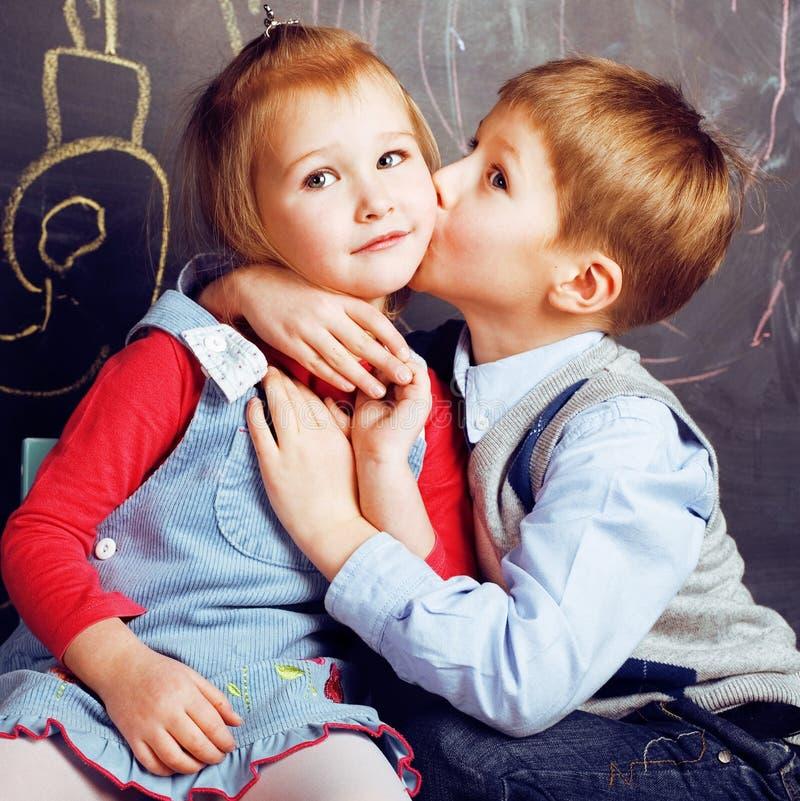 Mała śliczna chłopiec całowania blondynki dziewczyna w sala lekcyjnej przy blackboard, pierwszy szkolna miłość, stylu życia pojęc fotografia royalty free