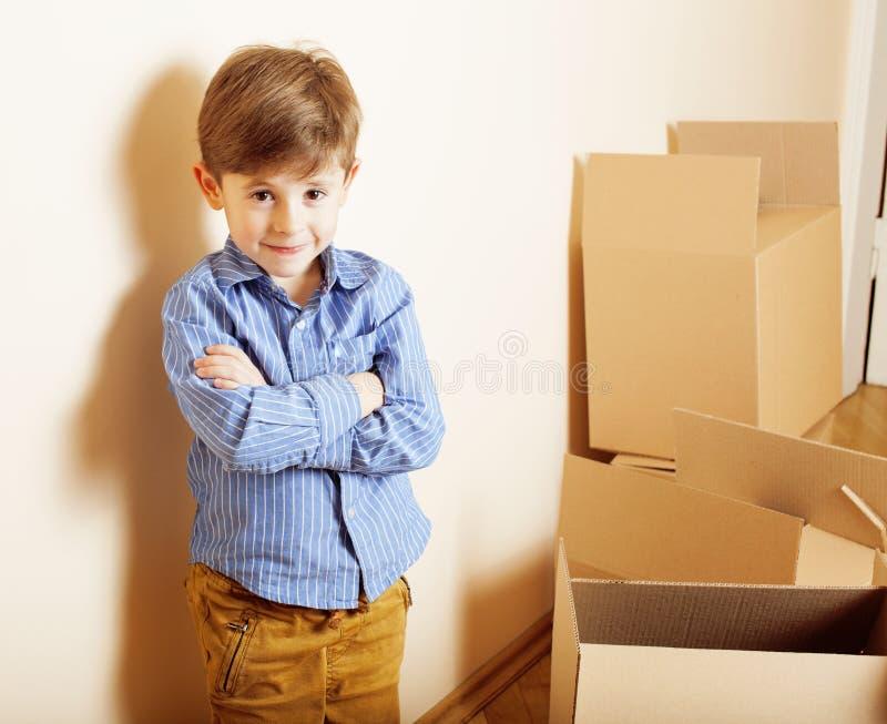 Mała śliczna chłopiec w pustym pokoju, remoove nowy dom dom samotnie wśród pudełek zamknięty up uśmiechnięty dzieciak, stylów życ fotografia stock