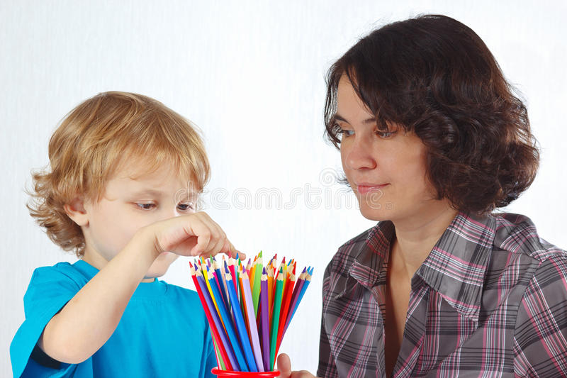 Mała śliczna chłopiec z jego matek spojrzeniami na kolorów ołówkach zdjęcia royalty free