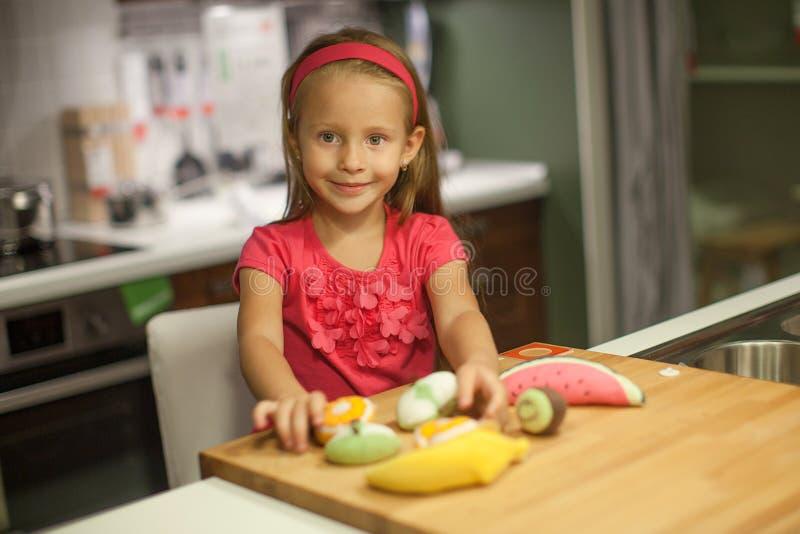 Mała śliczna dziewczyna bawić się w kuchni z obrazy royalty free