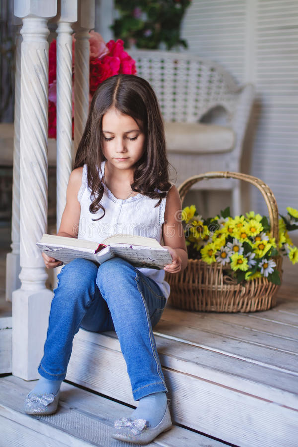 Mała śliczna dziewczyna czyta książkę obrazy royalty free