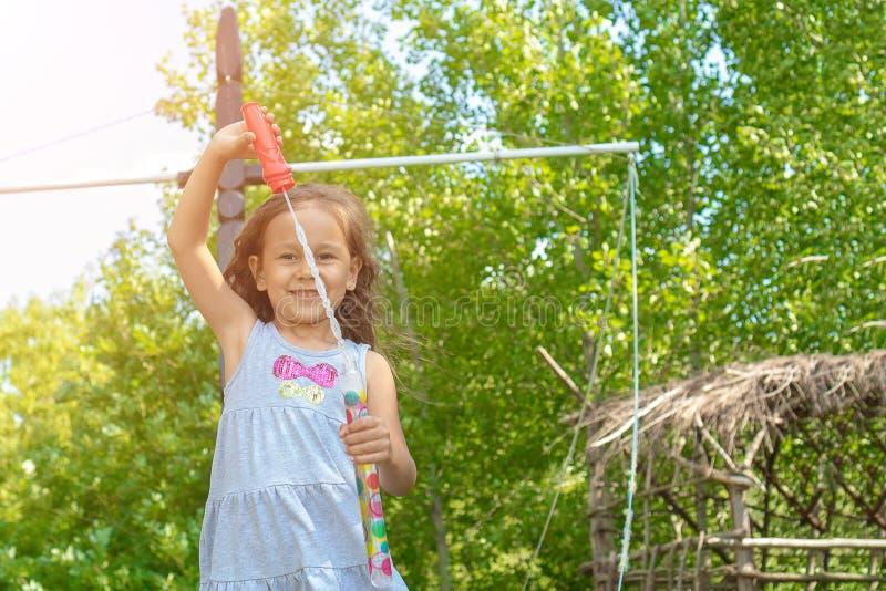 Mała śliczna dziewczyna dmucha mydlanych bąble jest uśmiechnięta fotografia stock