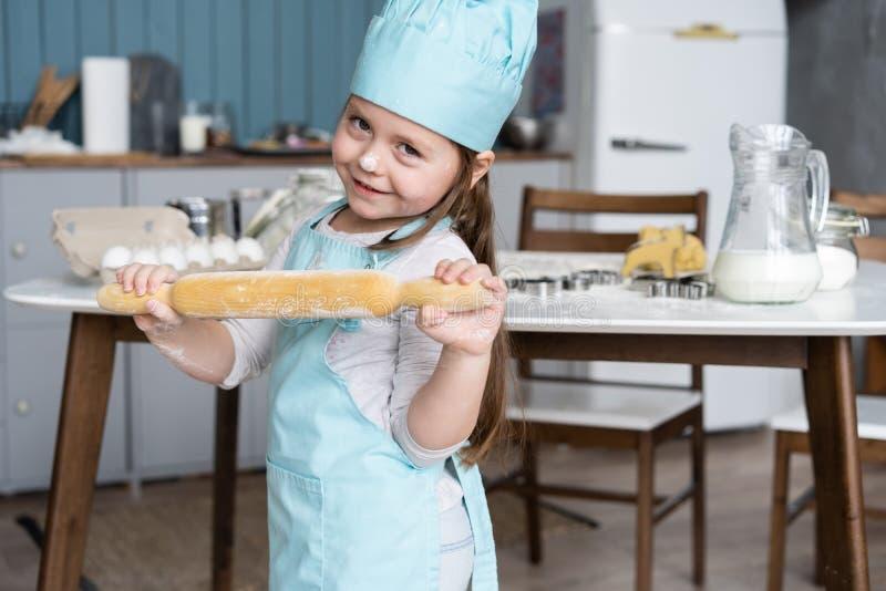 Mała Śliczna dziewczyna Gotuje Na kuchni Mieć zabawę podczas gdy robić tortom i ciastkom Uśmiechnięty i patrzejący kamerę obrazy stock
