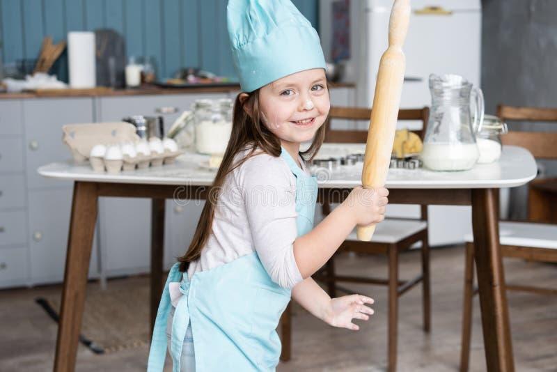 Mała Śliczna dziewczyna Gotuje Na kuchni Mieć zabawę podczas gdy robić tortom i ciastkom Uśmiechnięty i patrzejący kamerę zdjęcie stock