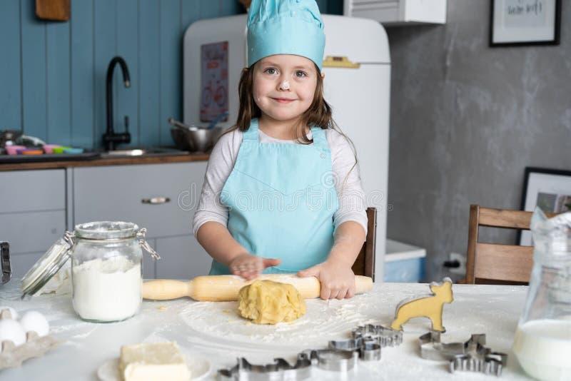 Mała Śliczna dziewczyna Gotuje Na kuchni Mieć zabawę podczas gdy robić tortom i ciastkom Uśmiechnięty i patrzejący kamerę zdjęcie royalty free