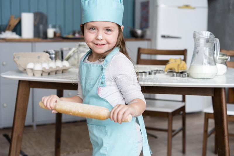 Mała Śliczna dziewczyna Gotuje Na kuchni Mieć zabawę podczas gdy robić tortom i ciastkom Uśmiechnięty i patrzejący kamerę zdjęcia royalty free