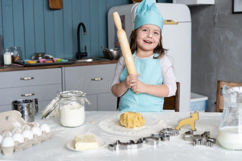 Mała Śliczna dziewczyna Gotuje Na kuchni Mieć zabawę podczas gdy robić tortom i ciastkom Uśmiechnięty i patrzejący kamerę obrazy royalty free
