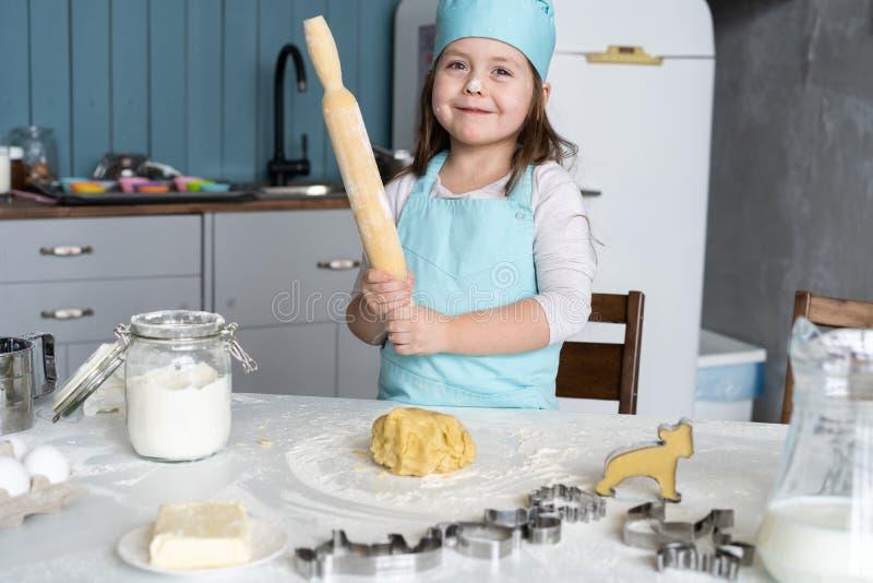 Mała Śliczna dziewczyna Gotuje Na kuchni Mieć zabawę podczas gdy robić tortom i ciastkom Uśmiechnięty i patrzejący kamerę zdjęcia stock